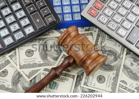Judge gavel, calculators and dollar banknotes - stock photo