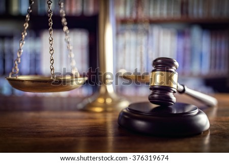 Judge gavel, scales of justice and law books in court - stock photo