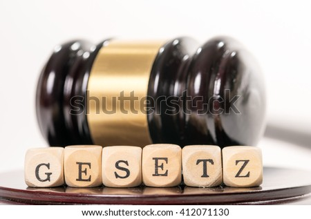 judge gavel with wooden letters and the german word law / Law