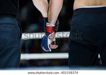 judge holds hand of  boxer before announcing winners in a fight - stock photo