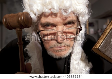 Judge. Old male judge in a courtroom striking the gavel - stock photo