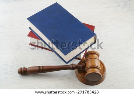 Judge's gavel and blue and red legal books - stock photo