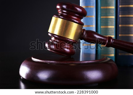 Judge's gavel and books on dark grey background - stock photo