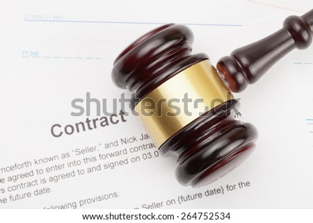 Judge's gavel and contract under it - stock photo