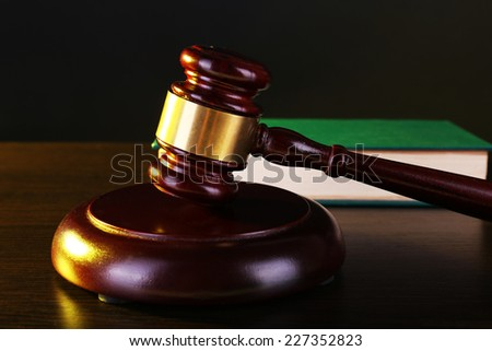 Judge's gavel and green book on dark grey background