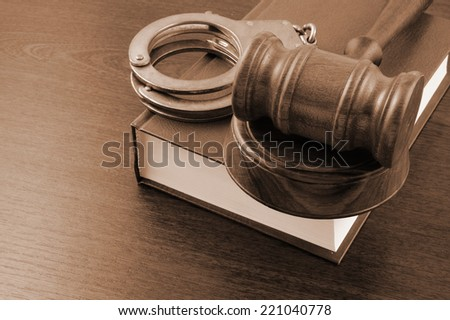 Judge's gavel and handcuffs on legal book  - stock photo