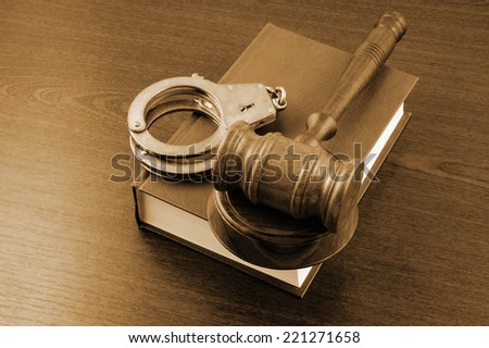 Judge's gavel and handcuffs on legal book