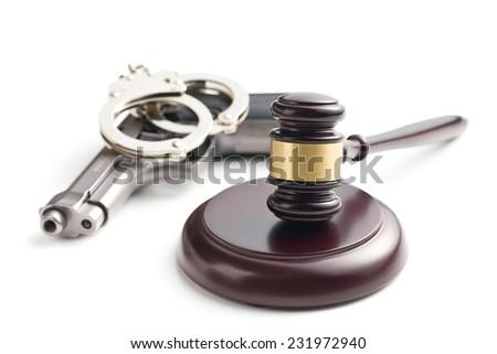 judge's gavel and handgun with handcuffs on white background - stock photo
