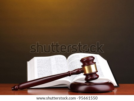 Judge's gavel and open book on wooden table on brown background - stock photo