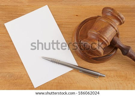 Judge's gavel, blank paper and silver pen on wooden table  - stock photo