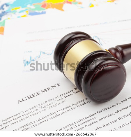 Judge's gavel over agreement documents and world map - close up shot