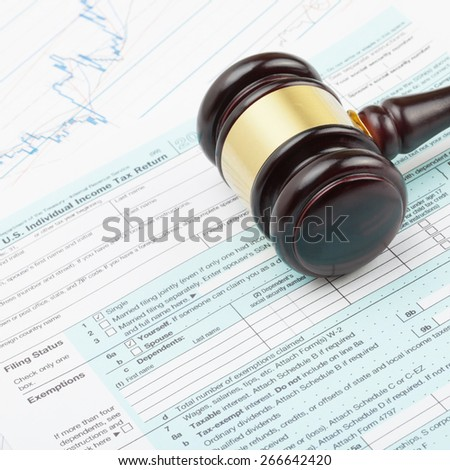 Judge's gavel over 1040 US Tax form - close up shot