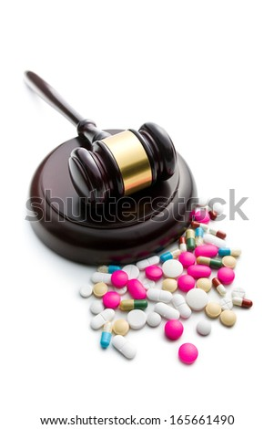 judge's gavel with pills on white background - stock photo