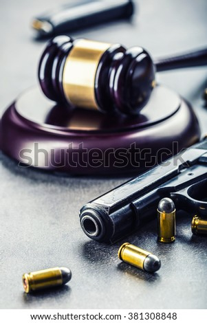 Judge's hammer gavel. Justice and gun. Justice and the judiciary in the unlawful use of of weapons. Judgment in murder. - stock photo