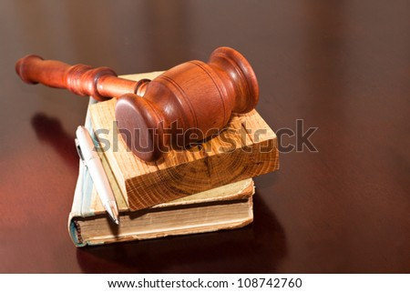 Judges gavel, book and pen on the table. - stock photo