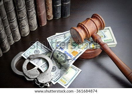 Judges Gavel, Handcuffs, Dollar Cash And Old Law Book  On The Black Wooden Table Background In The Back Light. Overhead View. - stock photo