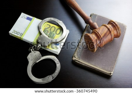 Judges Gavel, Handcuffs, Euro Cash And Old Law Book  On The Black Wooden Table Background In The Back Light. Overhead View. - stock photo