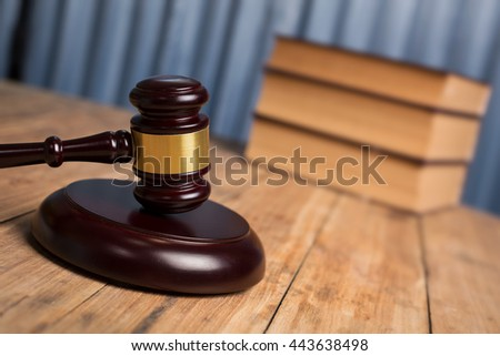 Judges gavel on old weathered wooden table, close up of photography. - stock photo