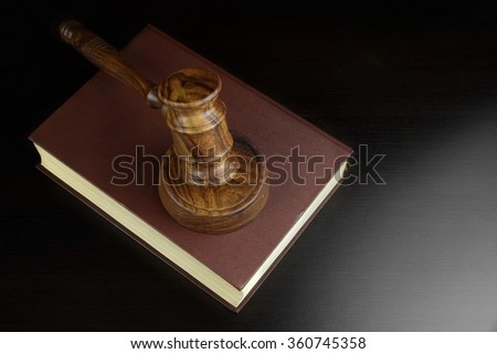 Judges Or Auctioneers Gavel And Red Legal Book On Black Table In The Back Light. Overhead View. Law Concept. - stock photo