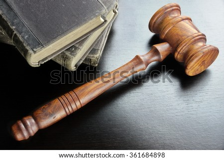 Judges  Or Auctioneers Walnut Gavel And Old Law Book  On The Black Wooden Table Background In The Back Light. Overhead View. Lawsuit or Auction Bidding Concept - stock photo
