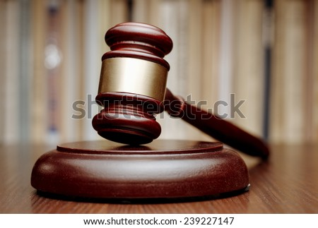 Judges wooden gavel with a decorative brass band resting on a wooden plinth on a table in court