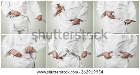 Judoka tying the white belt (obi) - stock photo