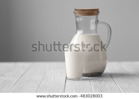 Jug and glass of fresh milk on white wooden table