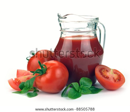 Jug, glass of tomato juice and fruits with green leaves on white