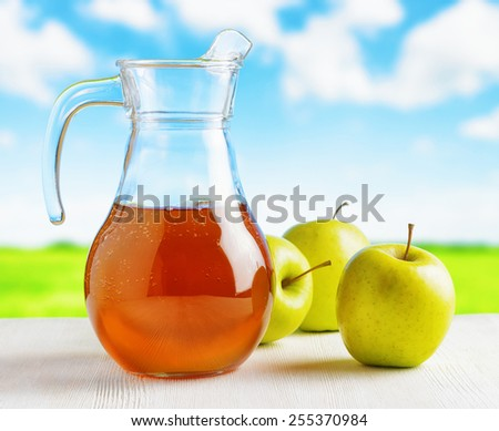 Jug of apple juice and green apples on meadow background. Eco food rich in minerals and vitamins. Product of organic farming. - stock photo