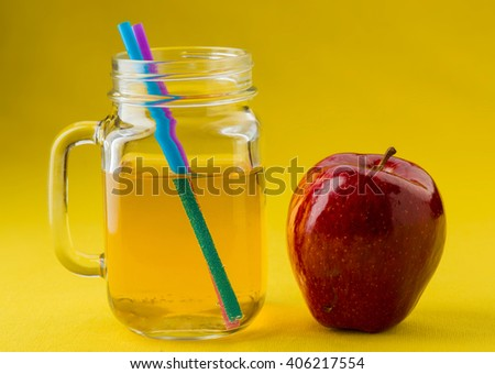 jug of apple juice on yellow tablecloth