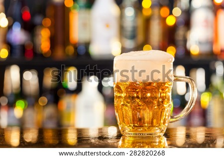 Jug of beer placed on bar counter with copy space - stock photo