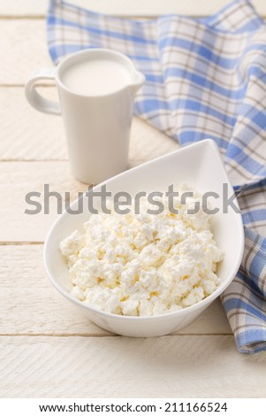 Jug of cream and cottage cheese on white wooden table - stock photo