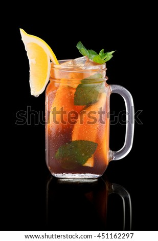 Jug of fresh cocktail with ice over black background