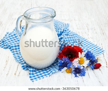 Jug of milk and wildflowers on a old wooden background - stock photo