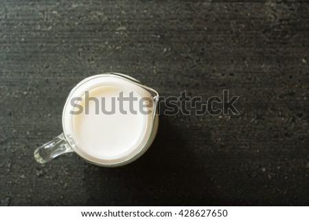 jug of milk on dark wooden table - stock photo