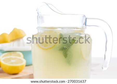 Jug of natural fresh lemonade on wooden table with the squeezer and somes lemons