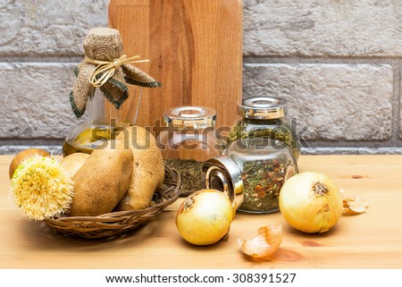 Jug of olive oil, potatoes, onion, cutting board and spices in the jars