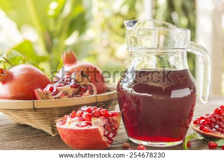 Jug of pomegranate juice with fresh fruits on wooden table. - stock photo