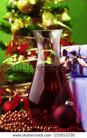 jug of rose wine and Christmas decoration against color background  - stock photo