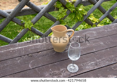jug of wine and a glass on a background of vineyard