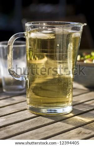 Jug with applejuice on a table outdoors