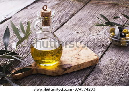 Jug with extra virgin olive oil on olive cutting board surrounded by branches of the olive tree and olives. Selective focus. The concept of a healthy natural food - stock photo