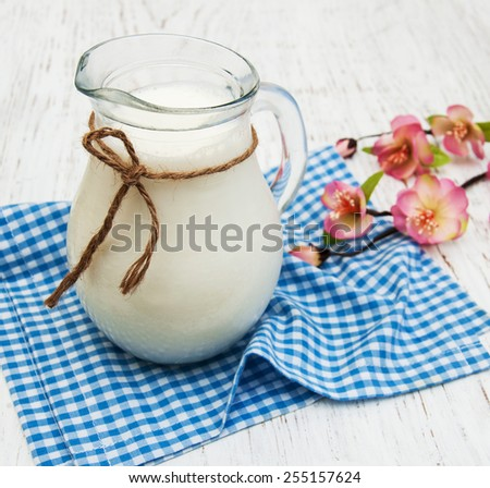 Jug with fresh milk and spring flowers