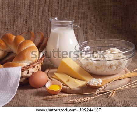 jug with milk, eggs, cheese, cottage cheese and bread on burlap background