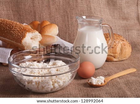jug with milk, eggs, cottage cheese and bread on burlap background