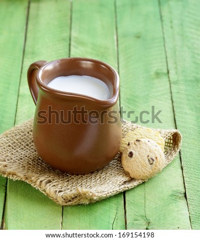 jug with milk on wooden table rustic still life