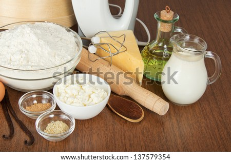 Jug with milk, sunflower oil, cottage cheese, a flour, a rolling pin and a mixer on a table