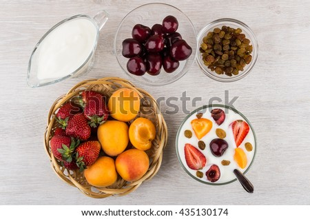 Jug with yoghurt, wicker basket with fruits and berries on table. Top view