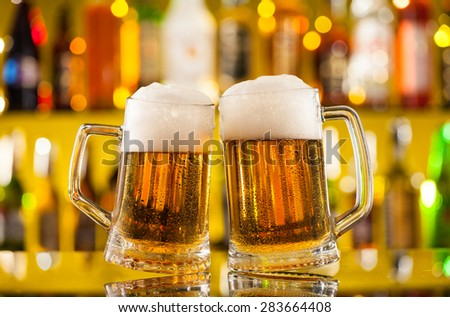 Jugs of beer placed on bar counter - stock photo