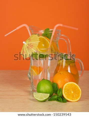 Jugs with drink and tea, a glass with an umbrella and straws, a citrus, on an orange background